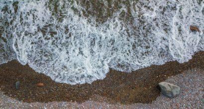 Flygfoto av havsvatten som flödar till en grusstrand.