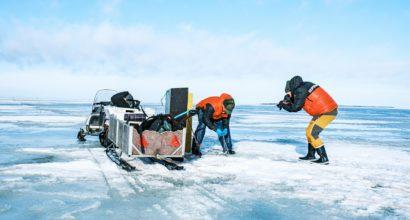 Videografen filmar ykresfiskare, som drar upp näten under isen.