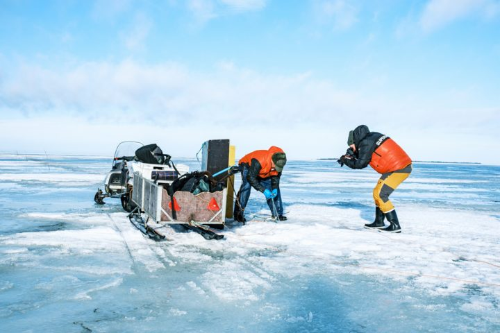 Videographer is filming professional fisherman, who is drawing up the nets from under the ice. There is also the fisherman's snowmobile and sleigh.